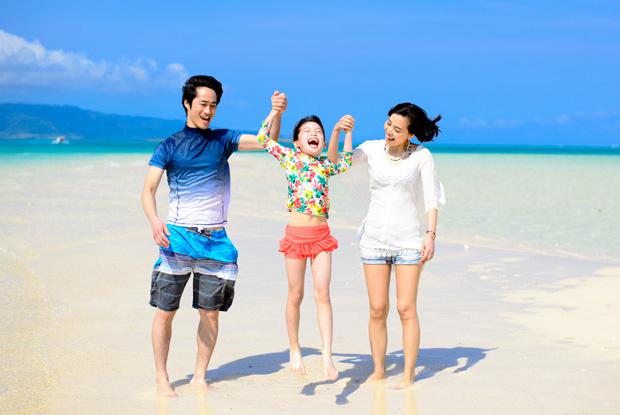 ビーチで子どもと遊ぶ家族