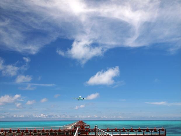 離陸して沖縄に向かって海上の空へ飛び立つ旅客機