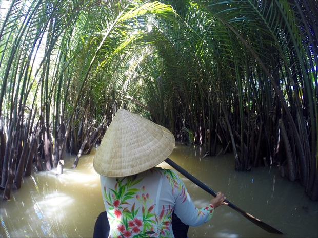 ベトナムの麦わら帽子ノラーをかぶり、漕ぎ進む船頭